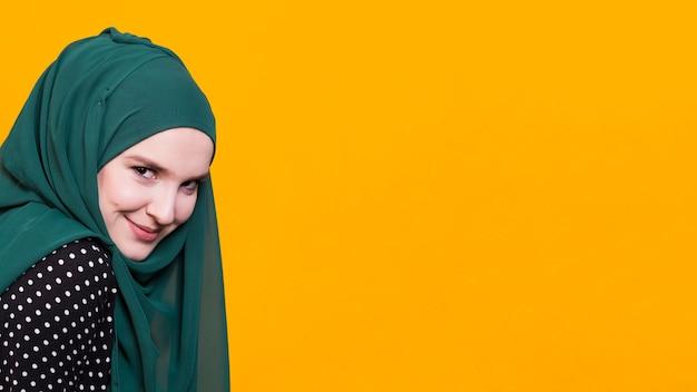 Vista frontal de la hermosa mujer sonriendo delante de fondo amarillo