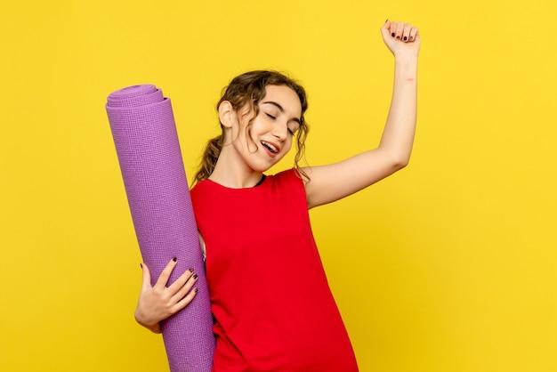 Vista frontal de la hermosa mujer sosteniendo alfombra púrpura sobre amarillo