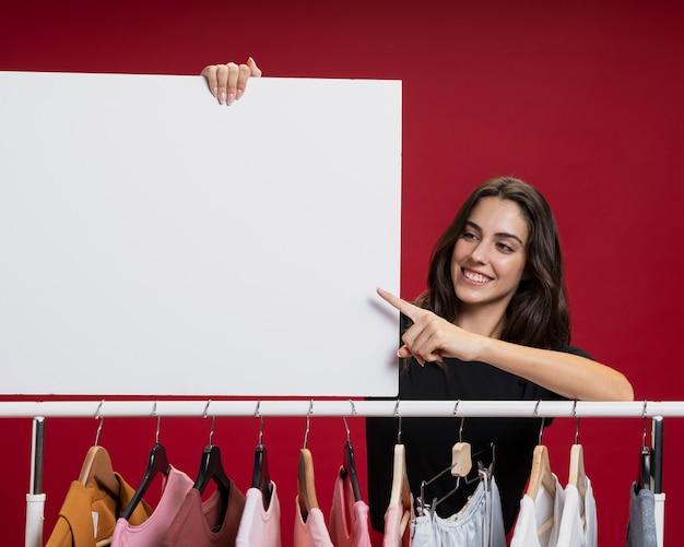 Vista frontal hermosa mujer sosteniendo una pancarta vacía