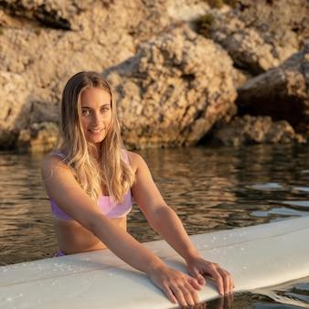Vista frontal de la hermosa mujer con tabla de surf