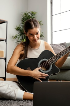 Vista frontal de la hermosa mujer tocando la guitarra