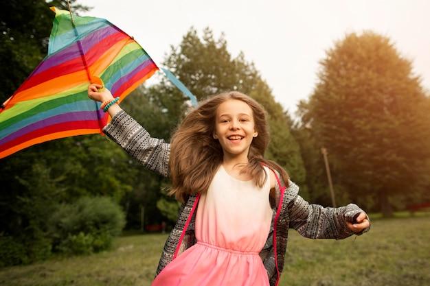 Vista frontal de la hermosa niña feliz con cometa