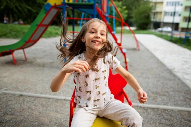 Vista frontal de la hermosa niña feliz en el parque