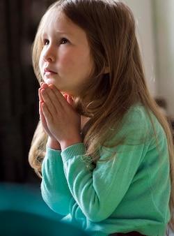 Vista frontal de la hermosa niña rezando