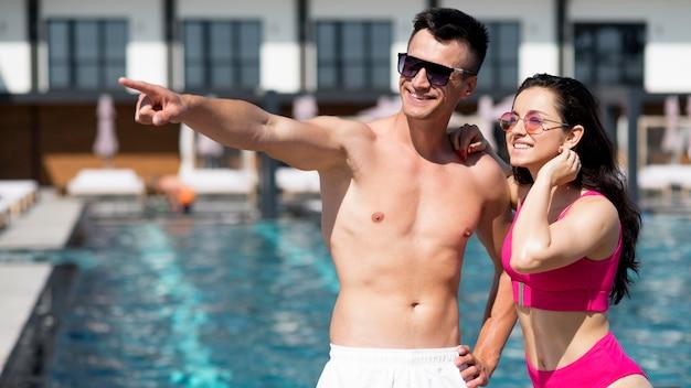 Vista frontal de la hermosa pareja en la piscina