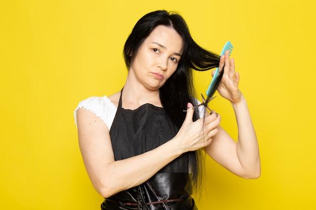 Una vista frontal hermosa peluquera en camiseta blanca capa negra con cepillos con el cabello lavado, cepillarse y cortar el cabello posando sobre el fondo amarillo estilista peluquero