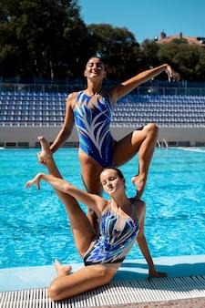 Vista frontal hermosas chicas posando junto a la piscina
