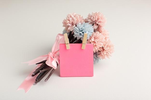 Vista frontal hermosas flores con pegatina rosa sobre superficie blanca