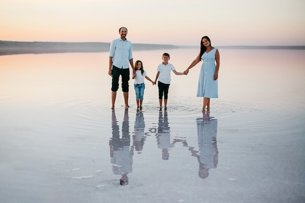 Vista frontal de hermosos padres jóvenes, su linda hijita e hijo tomados de la mano, caminando por la playa