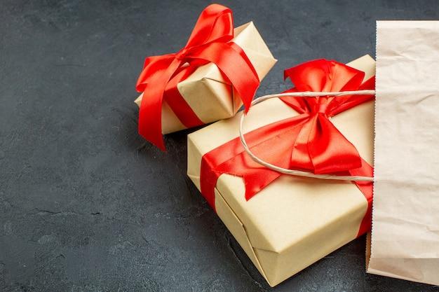 Vista frontal de hermosos regalos con cinta roja sobre una mesa oscura