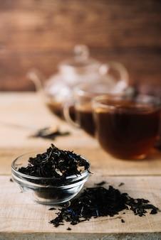 Vista frontal de hierbas de té negro con fondo borroso