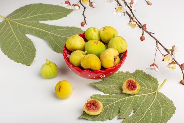 Vista frontal higos frescos fetos dulces y deliciosos dentro de la placa roja en el escritorio blanco