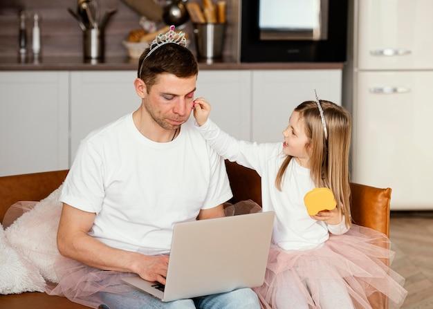 Vista frontal de la hija jugando con el padre mientras trabaja en la computadora portátil