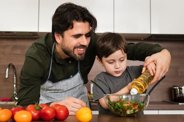 Vista frontal hijo ayudando a papá a hacer ensalada