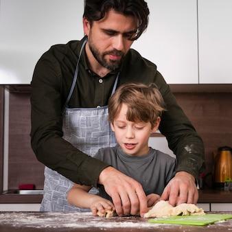 Vista frontal hijo y padre horneando en casa
