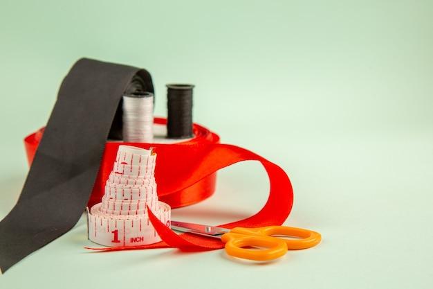 Vista frontal hilos de colores con lazo en la superficie verde ropa foto coser agujas coser alfileres de colores