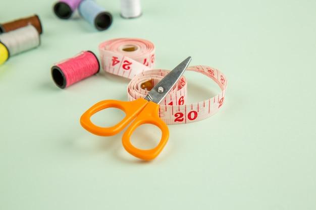 Vista frontal de hilos de colores sobre la superficie verde foto de coser coser agujas pin de ropa color