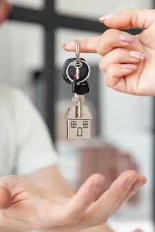 Vista frontal hombre aceptando las llaves para un nuevo primer plano de la casa