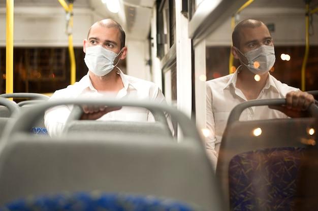 Vista frontal hombre adulto montando autobús con máscara médica