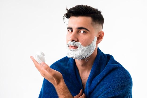 Vista frontal hombre afeitándose la barba mientras mira a la cámara