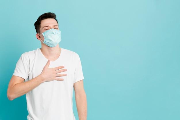 Vista frontal del hombre aliviado que llevaba una máscara médica
