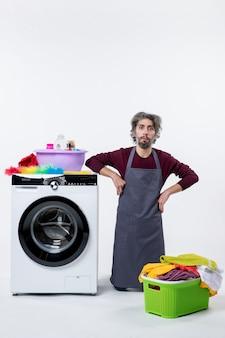 Vista frontal hombre de ama de llaves arrodillado cerca de la lavadora sobre fondo blanco.