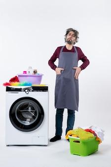Vista frontal hombre de ama de llaves determinado poniendo la mano en el bolsillo de pie cerca de la lavadora blanca sobre fondo blanco.