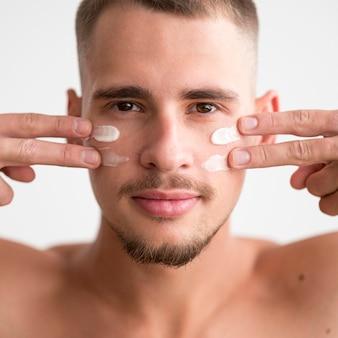 Vista frontal del hombre aplicando crema facial