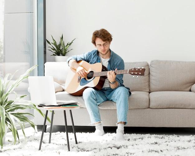 Vista frontal hombre aprendiendo guitarra en línea