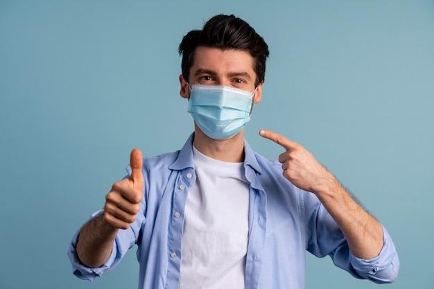 Vista frontal del hombre apuntando a la máscara médica que lleva y mostrando los pulgares hacia arriba
