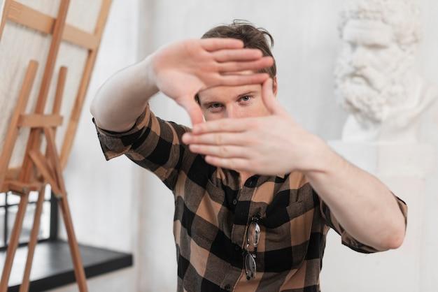 Vista frontal hombre artista haciendo un marco con sus dedos