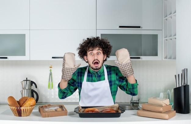 Vista frontal del hombre asustado con soporte de pie detrás de la mesa con pasteles recién horneados en la cocina blanca