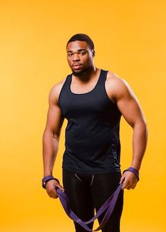 Vista frontal del hombre atlético en traje de gimnasio con banda de resistencia