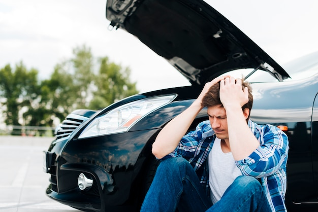 Vista frontal del hombre y auto negro