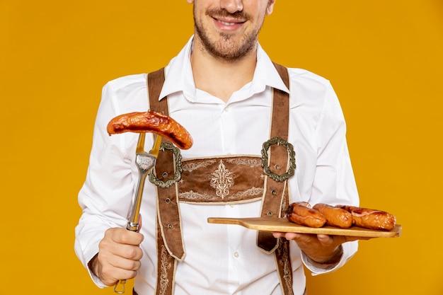 Vista frontal del hombre con bandeja de salchichas