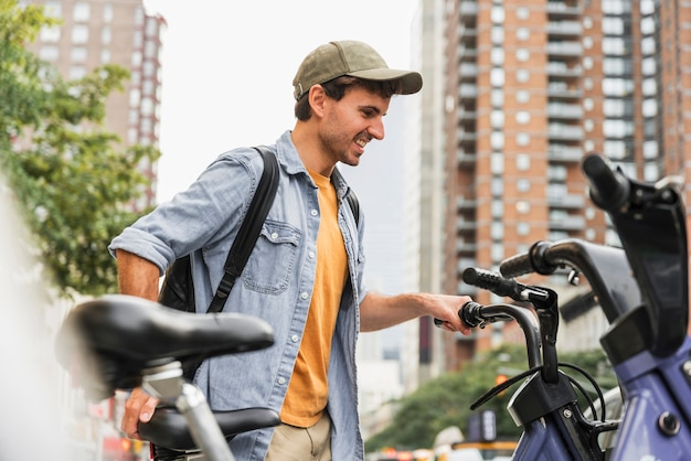 Vista frontal hombre con bicicleta en la ciudad