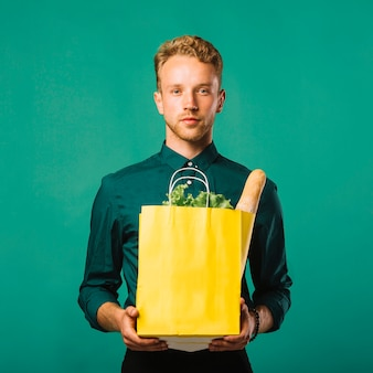 Vista frontal hombre bonito con bolsa de supermercado