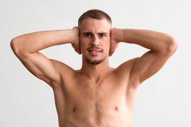 Vista frontal del hombre sin camisa mostrando sus bíceps mientras se cubre las orejas
