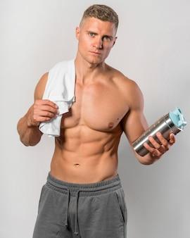 Vista frontal del hombre sin camisa posando con toalla y botella de agua