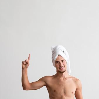 Vista frontal del hombre sin camisa con una toalla en la cabeza apuntando hacia arriba