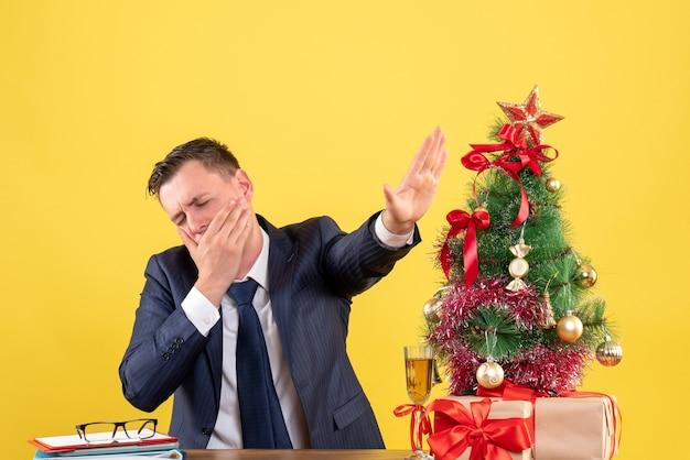 Vista frontal del hombre cansado bostezando mientras está sentado en la mesa cerca del árbol de navidad y regalos en amarillo