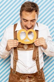 Vista frontal del hombre comiendo pretzel alemán