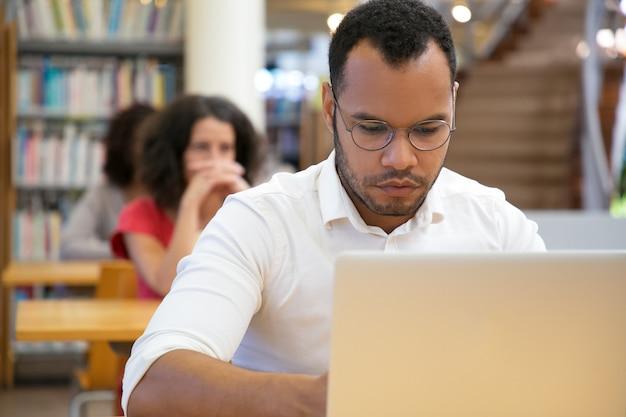 Vista frontal del hombre concentrado escribiendo en la computadora portátil