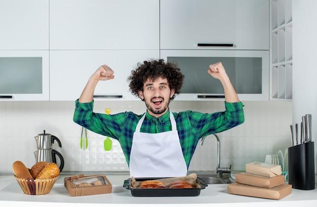 Vista frontal del hombre confiado de pie detrás de la mesa con pasteles recién horneados y mostrando su musculoso en la cocina blanca