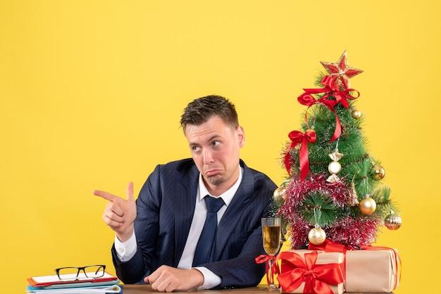 Vista frontal del hombre confundido apuntando a algo sentado en la mesa cerca del árbol de navidad y regalos en amarillo