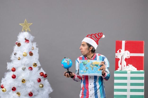Vista frontal hombre confundido con gorro de santa de resorte espiral sosteniendo mapa del mundo y globo cerca del árbol de navidad blanco
