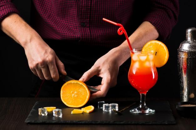 Vista frontal del hombre cortando naranja para cóctel