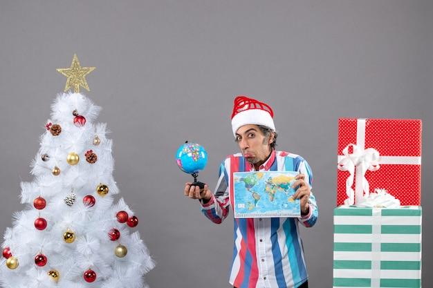Vista frontal del hombre curioso que sostiene el mapa del mundo y el globo cerca del árbol de navidad