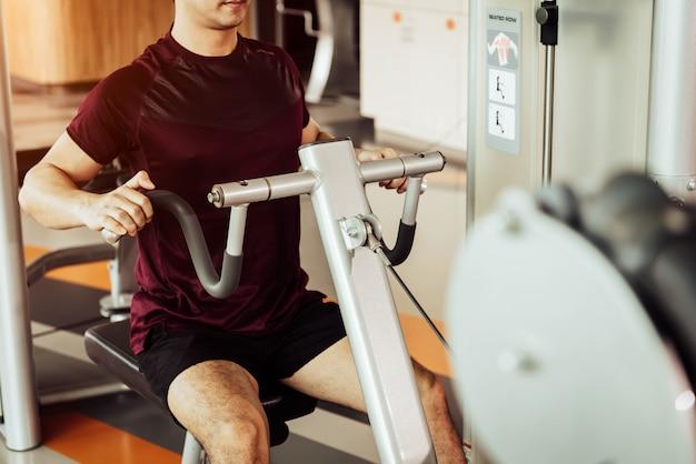 Vista frontal del hombre deportivo que usa la máquina de estiramiento de los músculos de la espalda llamada fila sentada en el gimnasio