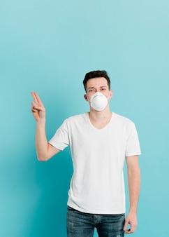 Vista frontal del hombre enfermo con máscara médica y apuntando con dos dedos hacia arriba